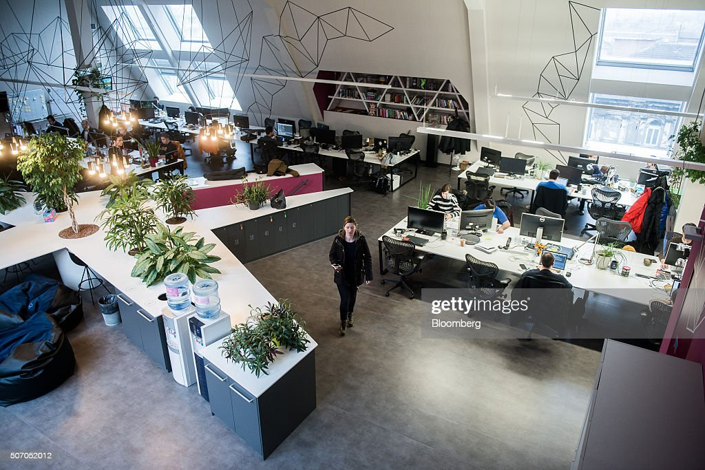 An employee walks through the office space as plants sit on desks inside the Ustream, Inc. office in Budapest, Hungary, on Tuesday, Jan. 26, 2016. International Business Machines Corporation (IBM) is buying live video stream provider Ustream to help sell more video services to clients including the National Football League, HBO and the Food Network, through its cloud platform. Photographer: Akos Stiller/Bloomberg via Getty Images
