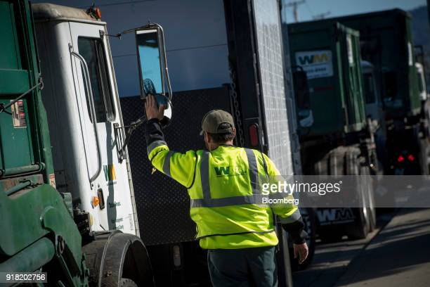 An employee walks towards a garbage collection truck outside the Waste Management Inc Davis Street Recycling Transfer Station in San Leandro...