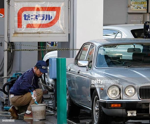 An employee washes a customer's vehicle at a TonenGeneral gas station in Tokyo Japan on Thursday Feb 14 2008 TonenGeneral Sekiyu KK a unit of Exxon...