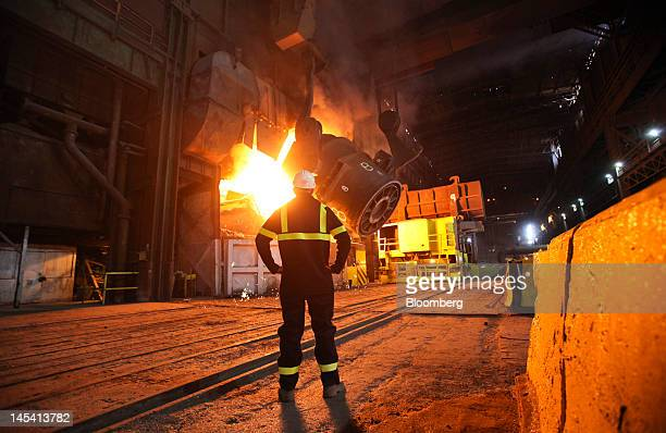 An employee watches a ladle pouring iron into the basic oxygen steelmaking vessel at the Sahaviriya Steel Industries Pcl steelmaking plant in Redcar...