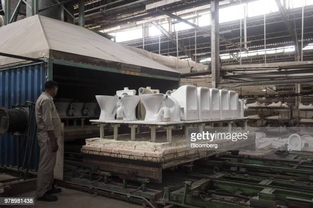 An employee watches a platform truck laden with glazed toilets enter a kiln at the HSIL Ltd factory in Bahadurgarh Haryana India on Monday June 11...