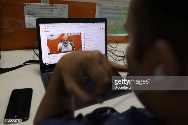 An employee watches a video clip featuring India's Prime Minister Narendra Modi while working work in the office of Vishwas News operated by Jagran...