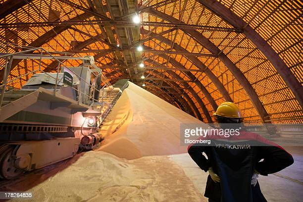 An employee watches as a machine deposits potash grain inside a storage facility operated by OAO Uralkali in Berezniki Russia on Monday Aug 26 2013...