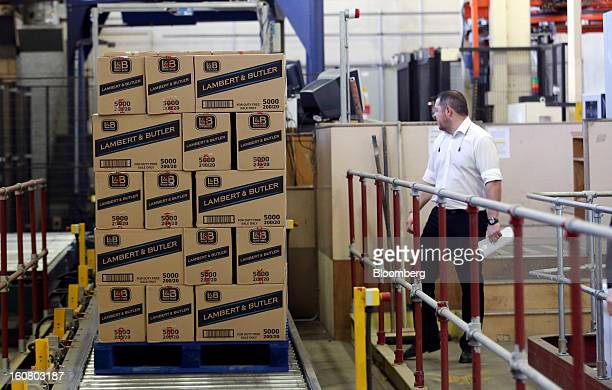 An employee watches as a pallet loaded with Lambert and Butler cigarettes moves along the production line ahead of distribution at Imperial Tobacco...