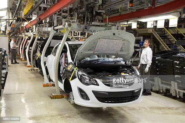 An employee watches as Opel Corsa automobiles move along the production line at the Adam Opel AG factory operated by General Motors Co in Eisenach...