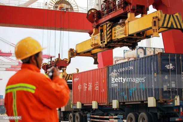 An employee watches over cranes as he talks on his interphone at a port in Qingdao east China's Shandong province on November 8 2018 China's exports...
