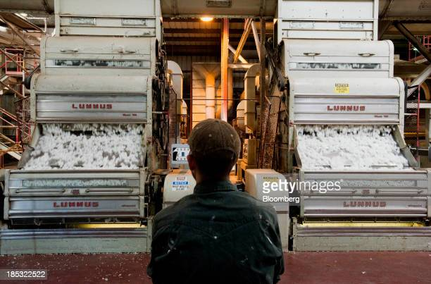 An employee watches over the cotton gin operation at Joe's Bayou Gin in East Carroll Parish Louisiana US on Wednesday Oct 9 2013 Parts of the...