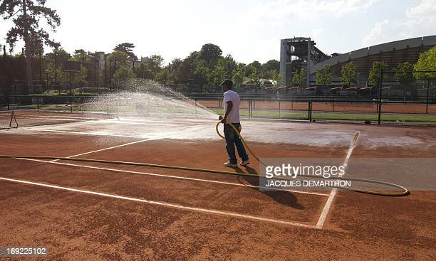 An employee waters a clay court of Roland Garros' stadium on April 20 2011 in Paris The Roland Garros event will run from May 17 to June 5 2011 AFP...