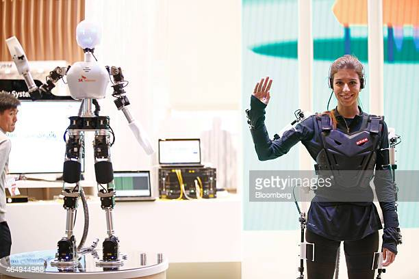 An employee waves her arm to demonstrate command of a 5G Mission Critical IoT wireless robotic device manufactured by SK Telecom Co at the Mobile...