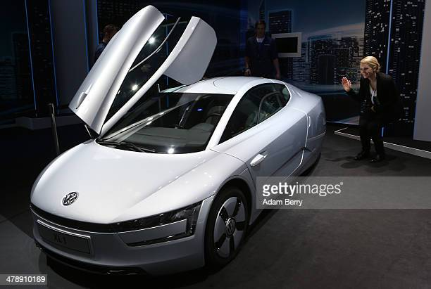 An employee waves to a visitor sitting inside of a Volkswagen XL1 plug-in diesel-electric hybrid automobile on display at the Electric Mobility Week...