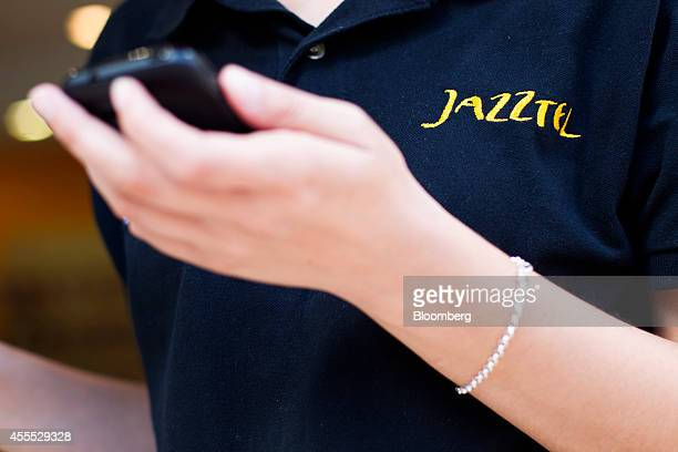 An employee wearing a branded polo shirt checks a mobile handset while working inside a franchised Jazztel phone store operated by Top Mobile in...