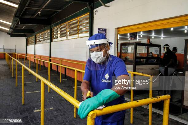 An employee wearing a face cleans a handrail at a popular soup kitchen on August 5, 2020 in Niteroi, Brazil. Employees received special training to...