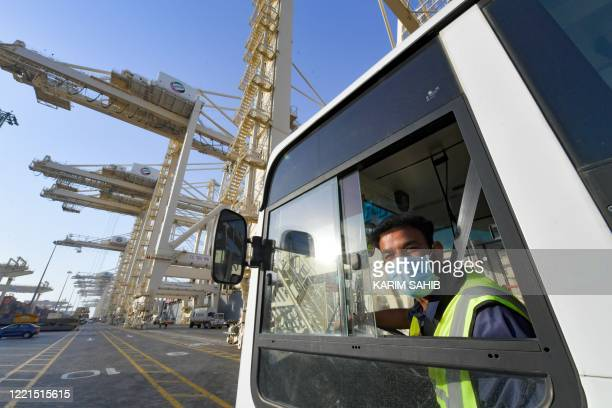 An employee wearing a face mask against the coronavirus works at the port of Jebel Ali operated by the Dubaibased giant ports operator DP World in...
