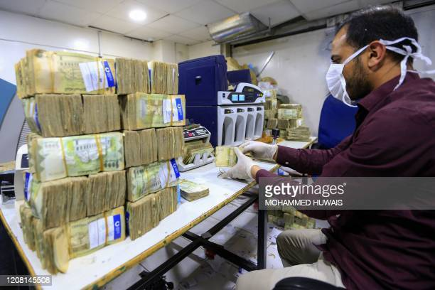An employee wearing a face mask and gloves counts local currency at a bank in the Yemeni capital Sanaa on March 24 2020 amid the COVID19 coronavirus...