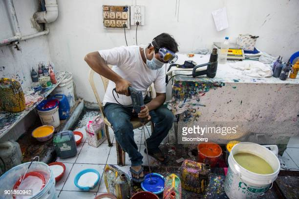 An employee wearing a face mask mixes screen printing fabric ink at a Rajlakshmi Cotton Mills Ltd garment factory in Kolkata West Bengal India on...