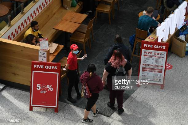 An employee wearing a face mask or covering due to the COVID19 pandemic welcomes customers to a Five Guys restaurant in Manchester northwest England...