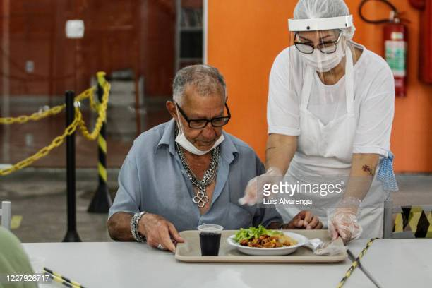 An employee wearing a face mask serves food on a table with alternating spaces at a popular soup kitchen on August 5, 2020 in Niteroi, Brazil....