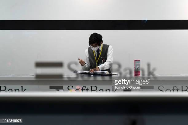 An employee wearing a face mask works in a SoftBank store on March 14 2020 in Osaka Japan Excluding the Diamond Princess cruise ship cases the number...
