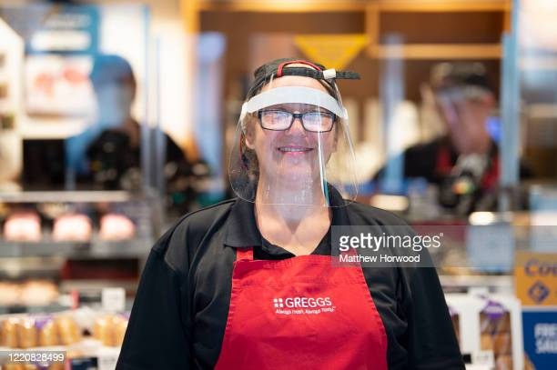 An employee wearing a face visor poses for a photograph at a Greggs store as the chain begins to reopen its stores as lockdown restrictions are eased...