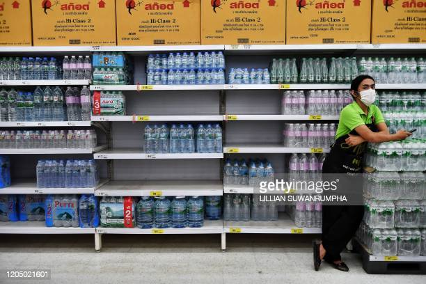 An employee wearing a facemask amid fears about the COVID19 novel coronavirus stands in front of shelves of bottled water in a supermarket in Bangkok...
