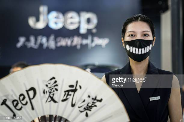 An employee wearing a mask as a precaution is seen in the Jeep stand during the 18th Central China International Auto Show on August 13, 2020 in...