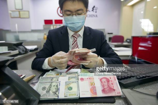 An employee wearing a mask deals with U.S. One-hundred dollar banknotes and Chinese one-hundred yuan banknotes at a branch of Bank of China on March...