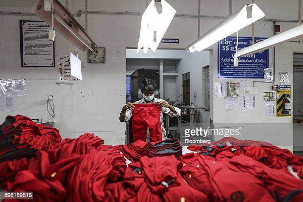 An employee wearing a mask handles garments on a production line at the CBC Fashions Pvt factory in Tiruppur Tamil Nadu India on Thursday Aug 4 2016...
