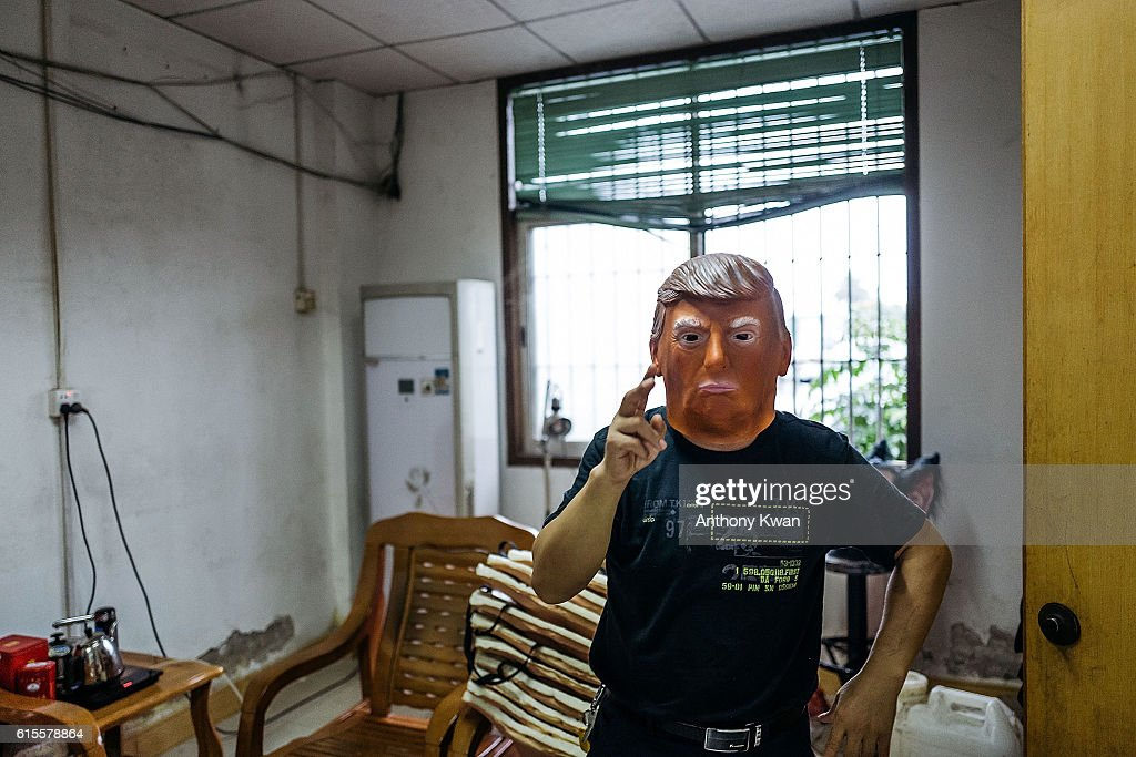 An employee wearing a mask of Donald Trump poses for a photograph at the Shenzhen Lanbingcai Latex Crafts Factory on October 18, 2016 in Shenzhen, China. Shenzhen Lanbingcai Latex Crafts Factory, located in the industrial area of Shenzhen with 20 to 30 employees, produces all sort of Halloween and party costumes and masks. It runs a small scale production of Donald Trump masks for local distribution within mainland China costing from 30 Renminbi onwards as the third Presidential Debate 2016 between Donald Trump and Hillary Clinton happens on Thursday. Chinese media have derided the election as a risible variety show in which the candidates' spectacular personal failings have taken precedence over the business of governance.