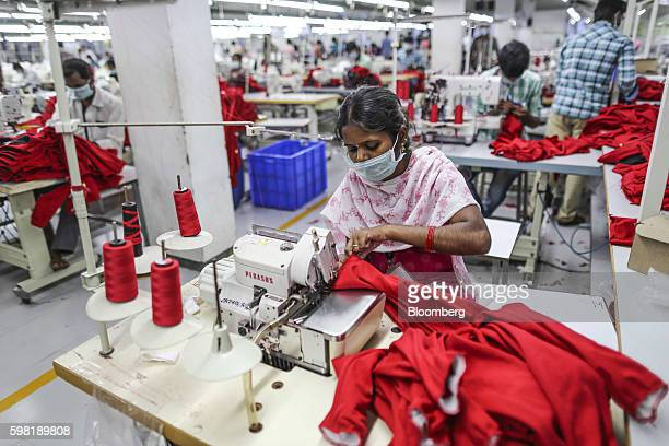 An employee wearing a mask uses a sewing machine on a production line at the CBC Fashions Pvt factory in Tiruppur Tamil Nadu India on Thursday Aug 4...