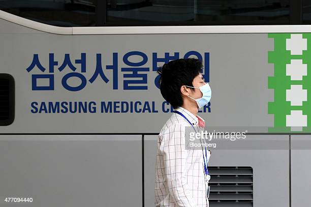 An employee wearing a mask walks past signage at the Samsung Medical Center in Seoul South Korea on Sunday June 14 2015 South Korea reported seven...