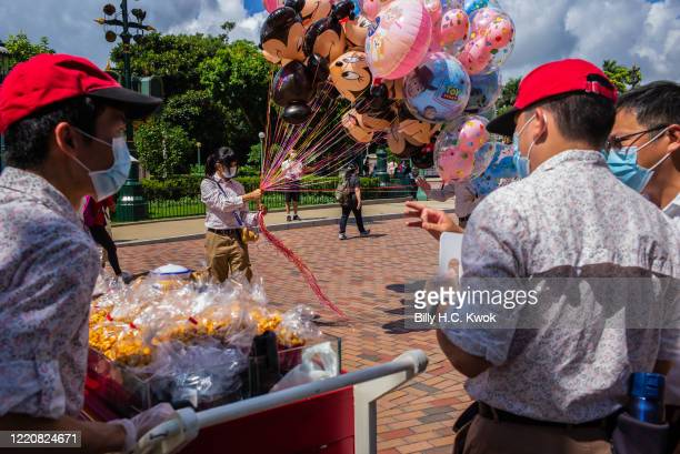 An employee wearing a protective face mask holds Mickey and Minnie Mouse balloons at Walt Disney Co's Disneyland Resort on June 18 2020 in Hong Kong...