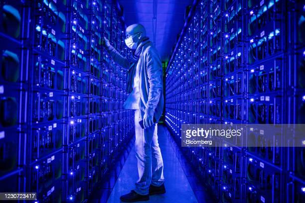 An employee wearing a protective face mask inspects mining rigs mining the Ethereum and Zilliqa cryptocurrencies at the Evobits crypto farm in...
