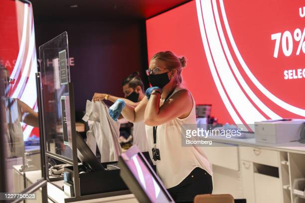 An employee wearing a protective face mask serves a customer from behind a perspex screen at the check out area inside a John Lewis Partnership Plc...