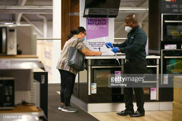 An employee wearing a protective face mask serves a customer wearing a protective face mask at a Currys PC World store, operated by Dixons Carphone...
