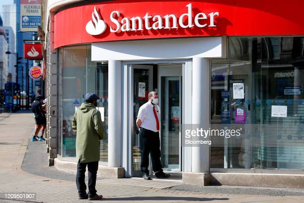 An employee, wearing a protective face mask, stands outside a Banco Santander SA bank branch in Manchester, U.K., on Wednesday, April 8, 2020. The...