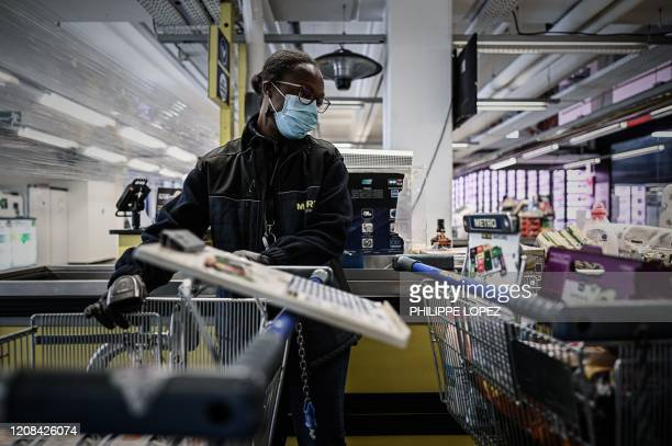 TOPSHOT An employee wearing a protective face mask works at the multinational wholesale chain METRO flagship shop in Nanterre on March 27 2020 during...
