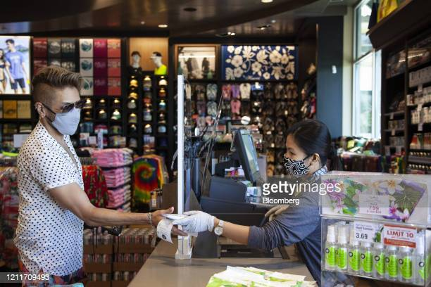 An employee wearing a protective mask and gloves hands a customer change at a market in Wailea Hawaii US on Sunday April 26 2020 Tourism makes up...