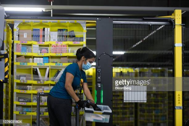 An employee wearing a protective mask prepares to place an item on to an automated stacking column at an Amazon.com Inc. Fulfillment center in...