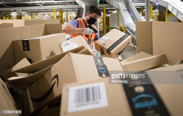 An employee wearing a protective mask scans a package at an Amazon.com Inc. Fulfillment center in Kegworth, U.K., on Monday, Oct. 12, 2020. Prime...