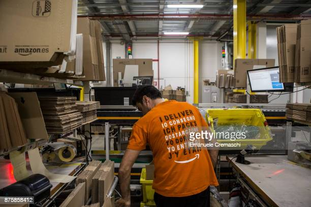 An employee wearing a tshirt reading 'I deliver' in several languages working at the Amazoncom MPX5 fulfillment center on November 17 2017 in Castel...