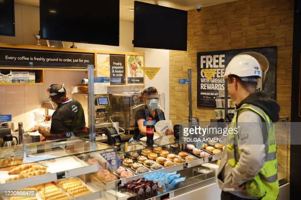An employee wearing PPE including a mask and visor serves a customer at the counter of a Greggs bakery in London on June 18, 2020 after the chain...