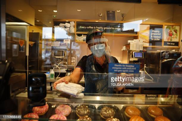An employee wearing PPE including a mask and visor serves at the counter of a Greggs bakery in London on June 18, 2020 after the chain reopened...