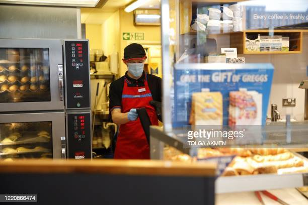 An employee wearing PPE including a mask works behind the counter of a Greggs bakery in London on June 18, 2020 after the chain reopened hundreds of...