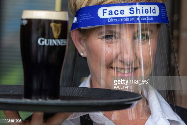 An employee wearing PPE , of a face shield or visor as a precautionary measure against spreading COVID-19, poses for a photograph with a customer's...