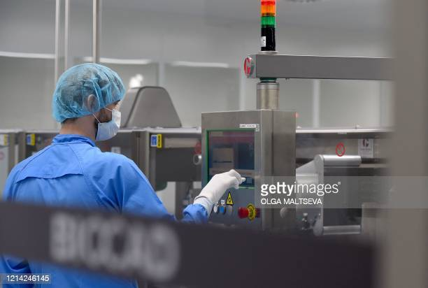 An employee wearing protective equipment works at the production line of Russia's biotech company BIOCAD, which is developing its own vaccine against...