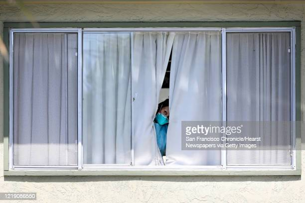 An employee wearing protective gear peeks from a window after a patient was picked up by Falcon Critical Care Transport at Gateway Care and...