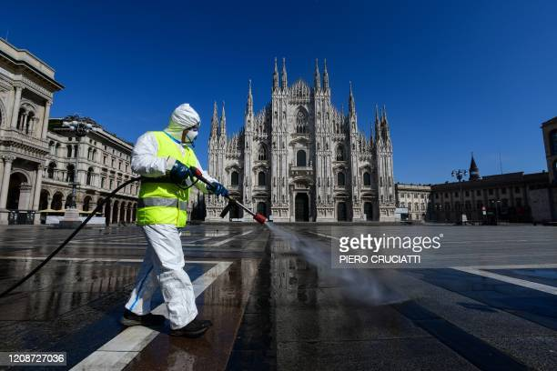 TOPSHOT An employee wearing protective gear working for environmental services company AMSA sprays disinfectant on Piazza Duomo in Milan on March 31...