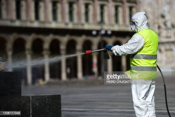 An employee wearing protective gear working for environmental services company AMSA sprays disinfectant on Piazza Duomo in Milan on March 31 2020...