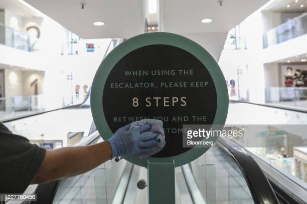 An employee wearing protective latex gloves sanitizes a social distancing sign inside a John Lewis Partnership Plc department store in London, U.K.,...