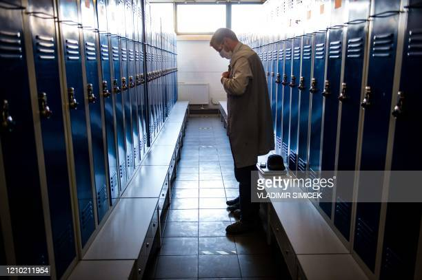 An employee wearing protective mask puts his coat on in the dressing room at the PSA Peugeot Citroen plant in Trnava, Slovakia, on April 17, 2020. -...